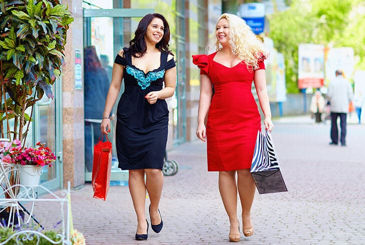 two women walking in the street wearing dresses