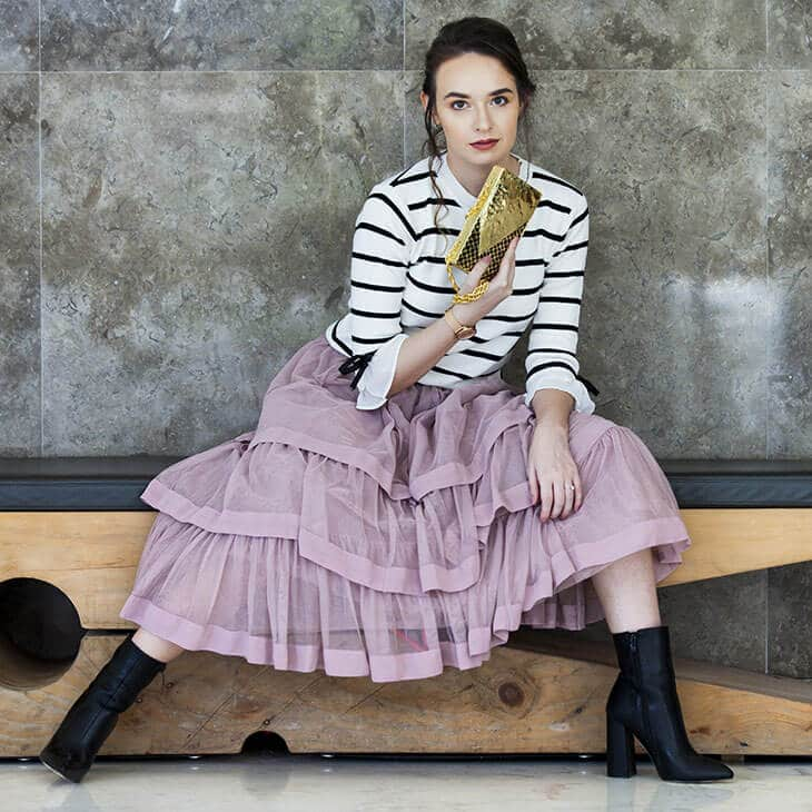 young woman sitting wearing a pink layered skirt