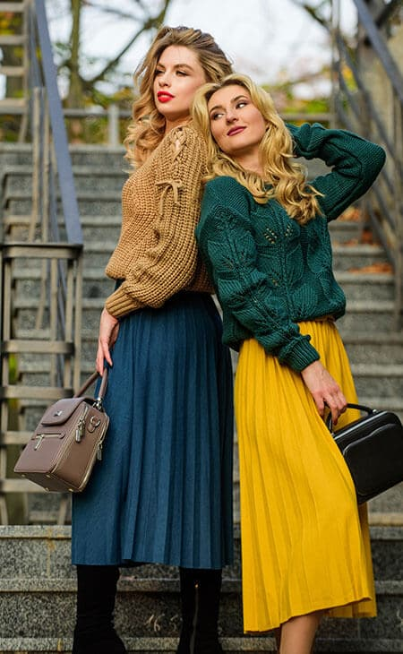 two beautiful women wearing pleated skirts